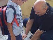 لقطة أبوية.. معلم يساعد تلميذه فى ربط الحذاء بسوهاج