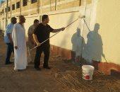 مدرسو مدرسة أحمد الشرباصى بالدقهلية يقومون بطلاء السور بأيديهم