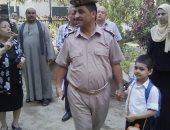 مأمور مركز شرطة ملوى بالمنيا يصطحب نجل شهيد إلى المدرسة