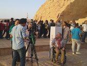 صور.. سياح يتابعون تعامد الشمس على وجه تمثال رمسيس الثانى فوق كرسى متحرك