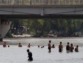 صور.. مهاجرو هندوراس يعبرون نهر كوسيتى للفرار إلى أمريكا بسبب الفقر والعنف