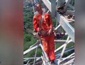 علقوا بأحزمة أمان..عمال صينيون ينامون على أبراج الكهرباء خلال الاستراحة