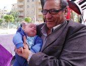 صور.. جد يحمل حفيده أثناء المشاركة فى استفتاء الدستور