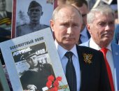"""صور.. بوتين يحمل صورة أبيه متصدرا مسيرة """"الفوج الخالد"""" خلال احتفالات عيد النصر"""