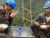 بأحزمة الأمان.. عمال كهرباء صينيون يناولون الطعام على ارتفاع 130 مترا..صور