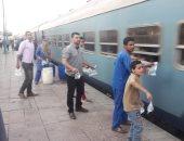 صور.. شباب متطوعون يوزعون وجبة إفطار على ركاب القطارات بمحطة الفشن