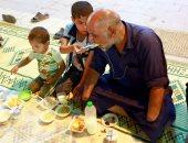 شاهد.. طفل عراقى يطعم والده المبتورة يداه فى إفطار رمضان