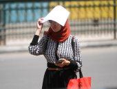 """صور.. المصريون يحتمون من الشمس بـ""""المذكرات والشنط وأكياس البلاستيك"""""""