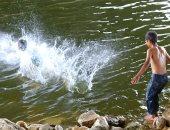 الأطفال يهربون من الموجة الحارة بالاستحمام فى نهر النيل