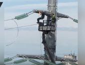 """شاهد.. مهندس كهرباء روسى يؤدى تمرين """"العقلة"""" على خطوط الجهد العالى"""
