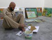 صور .. مواطن عراقى يهزم الإعاقة ويرسم 100 لوحة فنية بقدميه