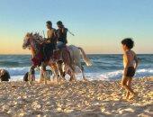 صور.. الخيل والجمال وسيلة ترفيه المصطافين على شاطئ العريش بشمال سيناء