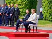 للمرة الأولى.. ميركل تحيى علم بلادها جالسة على كرسى