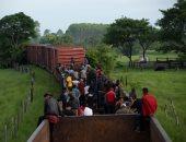 المهاجرون يتسلقون قطار شحن فى المكسيك للوصول للحدود الأمريكية