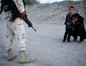 صورة بألف كلمة.. مهاجرة من جواتيمالا تصلى وتتوسل لضابط مكسيكى لدخول أمريكا