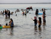 عراقيون يهربون من الحر الشديد بالسباحة فى بحيرة الحبانية