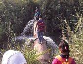 صور.. أطفال يسيرون على ماسورة لعبور ترعة بقرية المجابرة للوصول للمدرسة