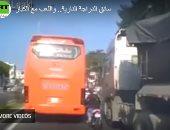 """""""اللعب مع الكبار"""".. سائق دراجة نارية يغامر بالعبور بين حافلة ضخمة وشاحنة (فيديو)"""