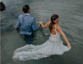 """""""عروسة البحر"""".. """"فوتوسيشن"""" ساحر لزوجين فى قلب الماء بملابس الزفاف"""