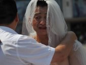 صينى يرتدى فستان زفاف لإنقاذ ابنته من سرطان الدم.. اعرف الحكاية