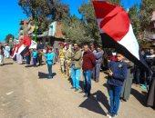 طلبة المدارس يصطفون رافعين الأعلام خلال تشييع جثمان الشهيد مصطفى عبيدو
