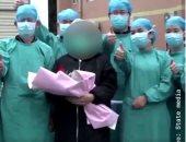 مرضى تعافوا من كورونا يلتقطون صورا مع الأطقم الطبية بمستشفى صيني.. فيديو