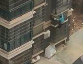 صينية مريضة بالفصام تهرب متسلقة الجدران إلى أسفل هربا من أبنها..فيديو وصور