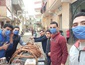 شباب قرية كفر الخوازم بالدقهلية يواجهون فيروس كورونا بتعقيم الشوارع والمنازل