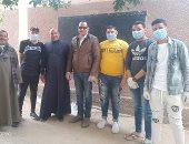 شباب قرية بنى حرام بالمنيا يطهرون الشوارع ويوزعون الكمامات على الأهالى