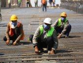 عمال العاصمة الإدارية يتحدون كورونا بالكمامات