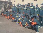 عمال النظافة بالكمامات خلال تطهير شوارع العريش