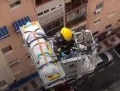 رجل إطفاء ينقل عجوزا فى التسعين مصابا بكورونا برافعة إنقاذ من منزله.. فيديو