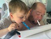 """أب """" قعيد"""" يستغل عزل كورونا لتعليم طفله الرسم بالفم .. صور"""
