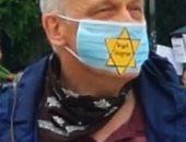 متظاهرون ألمان يرتدون كمامة طبية عليها شارة اليهود الصفراء في برلين