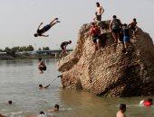 عراقيون يهربون من حرارة الجو إلى القفز فى نهر دجلة للسباحة وصيد الأسماك