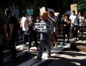 """متظاهرون بأقنعة وصور للرئيس الأمريكى فى مسيرة """"حقوق السود"""" بتايم سكوير"""
