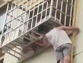 موقف بطولى من رجل صينى أنقذ طفلة تعلقت رأسها فى شرفة منزل.. شاهد عمل إيه