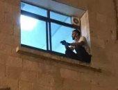 صورة متداولة لشاب يصعد لنافذة مستشفى عزل ليطمئن على والدته.. اعرف تفاصيلها