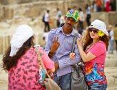 صورة اليوم.. سائحة تلتقط صورة تذكارية مع بائع مصرى بالهرم