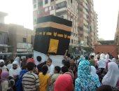 قارئ يشارك بصورة للأطفال فى مسيرة طواف حل مجسم الكعبة بالمعصرة