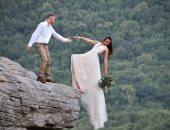 عروسان يخضعان لجلسة تصوير خطيرة على حافة جرف بأمريكا.. صور