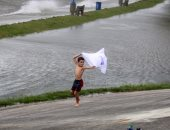 """صور.. أمريكيون يلهون وسط مياه إعصار """"سالى"""" فى الساحل الغربي للبلاد"""