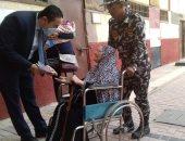 رئيس لجنة فرعية يخرج لمساعدة سيدة مسنة في الإدلاء بصوتها بالإسكندرية.. صور
