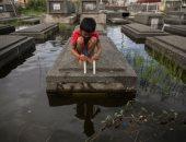 """صور.. مياه إعصار """"مولاف"""" في الفلبين تغرق المقابر"""