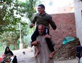 التضامن تستجيب لليوم السابع وتدعم الأب حامل ابنه بكرسى متحرك ومساعدة مالية