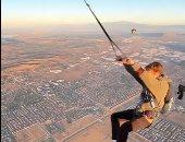 شاب متهور ينفذ قفزة بالمظلة من منطاد على ارتفاع 4 آلاف قدم بعد تأرجحه.. فيديو