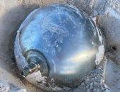 بريطانية تكتشف كرة تيتانيوم غريبة على الشاطئ مدون عليها بالروسية