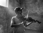 """100 صورة عالمية.. """"لحن الأمل"""" طفل يعزف وسط الحروب"""