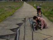 فنان صيني يرسم لوحات وهمية لطرق وحفر تخدع أبصار المارة.. فيديو