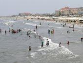 المئات على شاطئ بورسعيد هربًا من ارتفاع درجات الحرارة.. لايف وصور